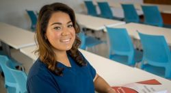 Photo of femalre student in scrubs in classroom in School of Nursing