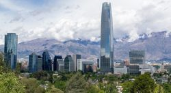 Photo of cityscape of Chile's capital city of Santiago. Tall buildings, trees, mountains and clouds