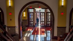 Student walking into Feliciano School of Business lobby backlit by sunrise