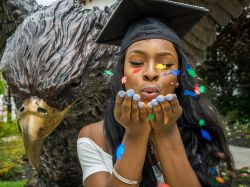 Montclair State University female student, wearing graduation cap, blowing confetti.