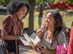 Two female Montclair State University students laughing together