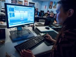 Female Montclair State University student using computer in 3D animation class.