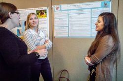 Photo of Jacqueline Lawrence, left, talks with partners Emily Baeli and Holly Kobezak about their research on the mental health of first responders.