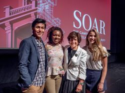 President Cole with students in front of a screen with SOAR campaign graphic