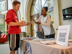 Britah Odondi, a graduate student working for the Office of Civic and Voter Engagement, helps sophomore Killian Ramsthaler register to vote.