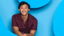 New Blues Clues host and MSU alum Joshua Dela Cruz smiling in front of blue background.