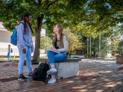 Two female Montclair State University students having conversation on campus
