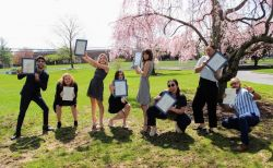 Students holding up certificates on grass