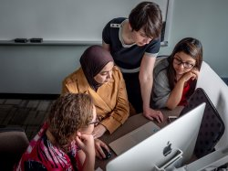 Professor with three female students in front of computer