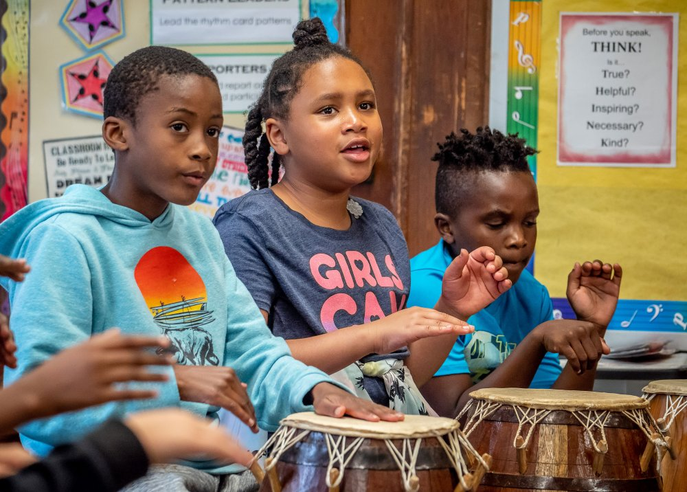 Three third grade students playing West African drums in classroom