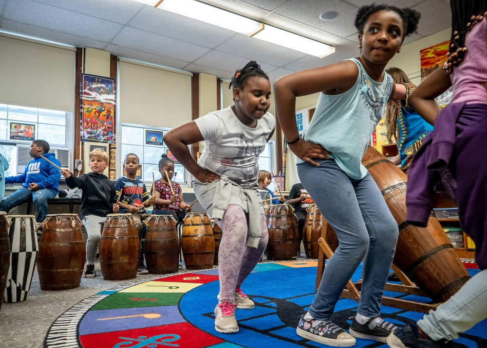 Third grade students dancing and playing West African drums in classroom