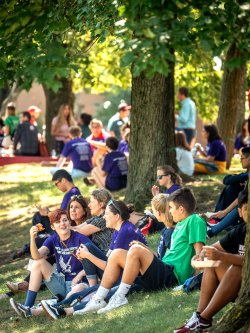 Students sitting under trees on quad
