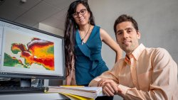 Environmental Studies Assistant Professor Jorge Lorenzo Trueba and doctoral candidate Isamar Marie Cortés in front of map