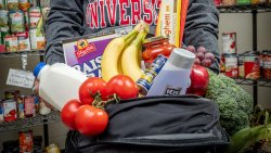 University student holding backpack filled with produce and other food in the Red Hawk Food Pantry