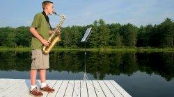 saxophonist on dock over lake
