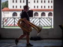 a student walks in a parking garage with tuba and music stand