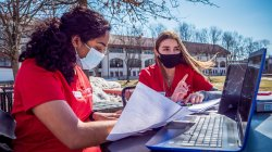 Two students in face masks using laptop outside in main quad