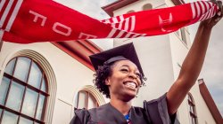 Recent graduate in cap and gown waving eof scarf above her head