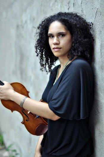 Jessie Montgomery leaning on wall holding violin