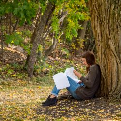 Student sitting against tree in wooded area on campus.