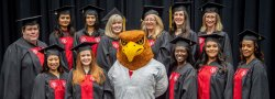 Nursing students posing with Rocky the Red Hawk at the School of Nursing Convocation.