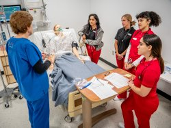 Nursing students gathered around medical manikin in simulation lab.