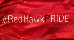 "Closeup of red riding jersey with black and white lettering spelling out ""#RedHawkPride""."