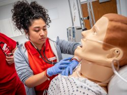 Female nursing student in simulation lab with medical manikin.