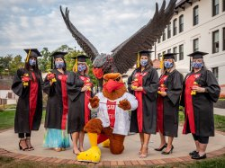 Faculty, students, and Rocky posing for celebratory photograph following commencement.