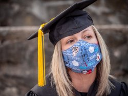 Female nursing student wearing graduation regalia and protective face mask.