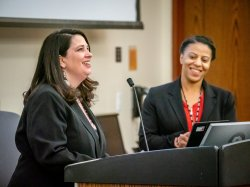 Dr. Nastassia Davis and Jill Wodnick standing behind a podium with a microphone.