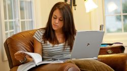 Student at home with laptop and textbook