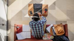 overhead photo of student on couch in a campus lounge using his laptop