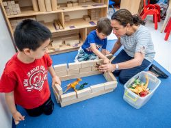 Teacher working with two children in children's center.