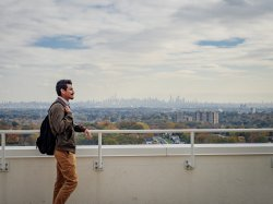Graduate student standing outside on green roof of CELS overlooking New York City skyline.