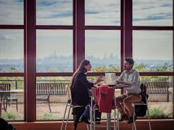Two students sitting down at a table in CELS with the skyline in the background.