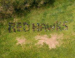 Students spelling out the word Red Hawks in the grass.