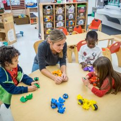 Photo of teacher with young children and blocks in classroom.