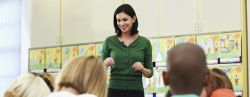 Woman wearing green sweater in classroom.