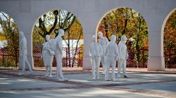 Photos of white statues that look like people milling around on the Montclair State campus.