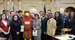New Jersey State Senate President Richard J. Codey (center) mugs for the camera between President Susan A. Cole and Rocky the Red Hawk surrounded by Montclair State students at the State House in Trenton.