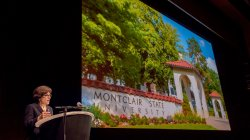 President Susan Cole speaking in front of a large screen with a photo of the Montclair State University entrance in Spring.