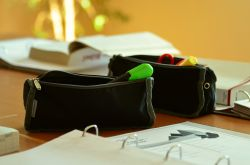 pencil cases and binders on a desk