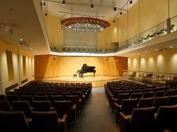 Piano on lit stage at John J Cali School of Music, Leshowitz Hall.