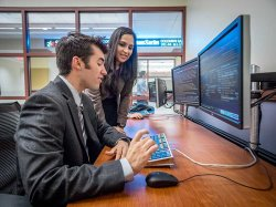 Students from the Feliciano School of Business analyzing stocks on double monitors.