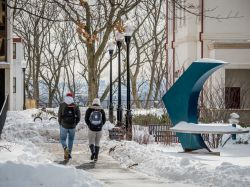 students walking through campus in the snow