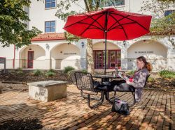 A student sitting outside of the School of Nursing and Graduate School reading a book on a sunny day under a table umbrella.