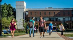 Students walking along the path in front of the CELS building on a sunny day.