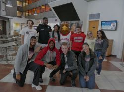 Students hanging out with Rocky the Red Hawk in the Blanton Hall atrium.