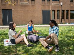 Students sitting in the grass outside of Calcia Hall having a conversation.